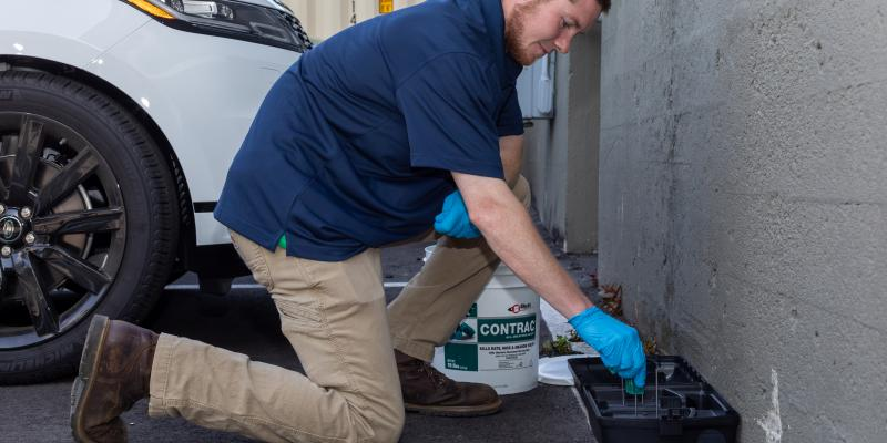 Exterminator from Clancy Bros Pest Control placing baiting and trapping tools around the exterior of a building.